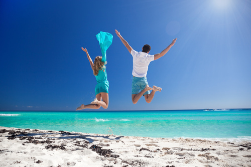 Happy couple jumping on beach