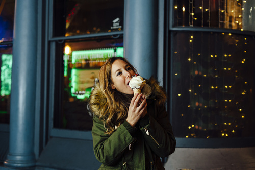 Young blonde woman eating ice cream at night with Christmas ligh