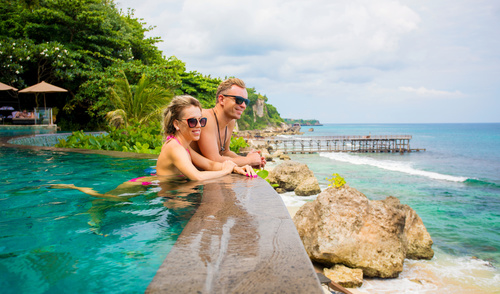 Couple relaxing in tropical swimming pool
